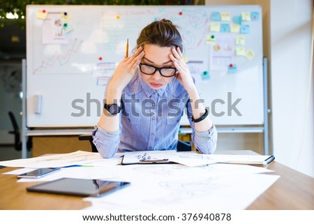 Exhausted young woman fashion designer sitting in office and drawing sketches - stock photo
