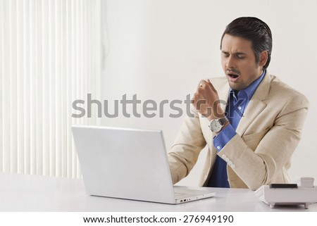Exhaustion young businessman using laptop at office desk