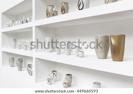Exhibition of funerary urns, propped on a shelf white.
