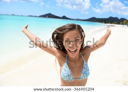 Exhilarated young woman screaming on beach. Portrait of cheerful female in bikini enjoying her summer vacation. Attractive tourist is standing with arms outstretched in nature. - stock photo