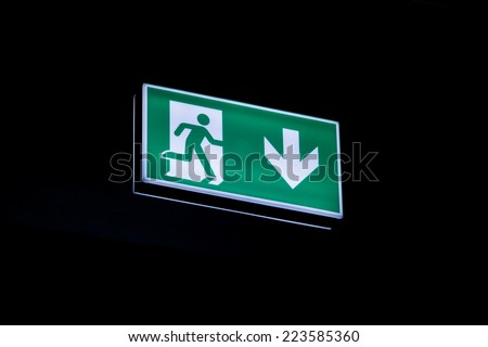Exit sign hanging on the ceiling of a parking garage. In the dark illuminated green and white symbol. - stock photo