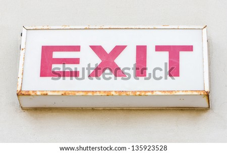 Exit sign on the concrete wall. - stock photo