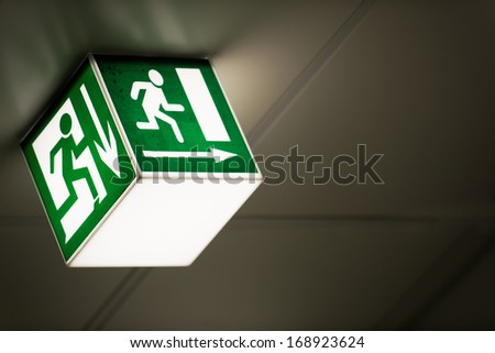 Exit sign on the wall - stock photo
