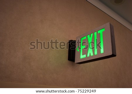 Exit sign points the way out of building at the airport - stock photo