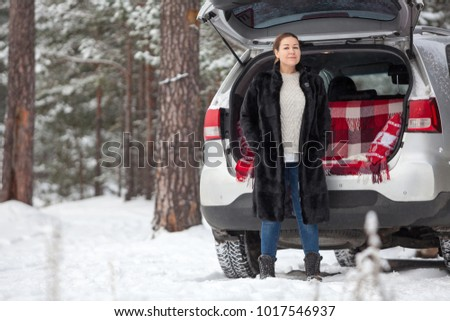Exited adult Caucasian woman in unbutton fur coat stands full-length near own car. Walking in wintry forest. Copy space