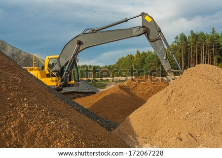 exkavator working with sand and gravel - stock photo