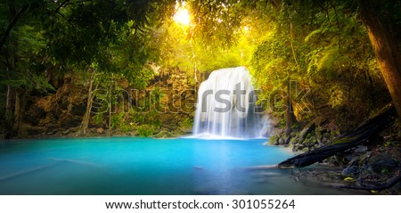 Exotic background of beautiful jungle forest with majestic waterfall falling into blue water lake and sun light rays shining through green leaves of tropical plants ant trees. Rainforest panorama - stock photo