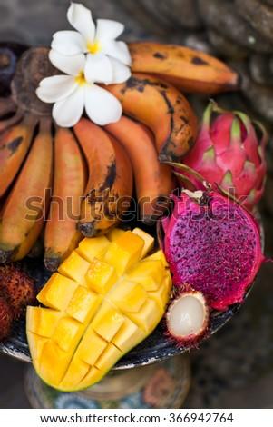 Exotic Bali Fruit Dish with Red bananas, Dragon Fruit, Pitaya and Rambutan. Breakfast on wood balineze plate - stock photo
