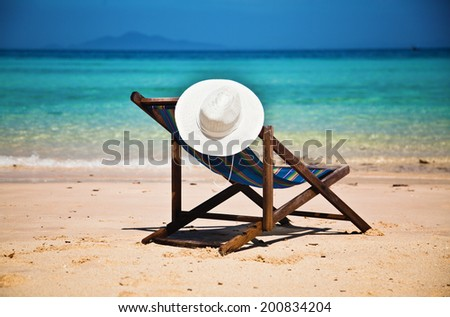 Exotic beach holiday background with beach chair - stock photo