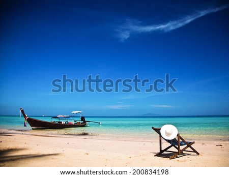 Exotic beach holiday background with beach chair and long tail boat - Thailand ocean landscape - stock photo