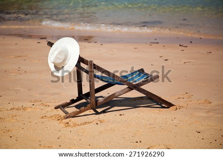 Exotic beach holiday background with white hate on beach chair - stock photo