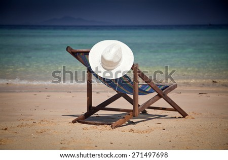 Exotic beach holiday - beach chair and hat - stock photo