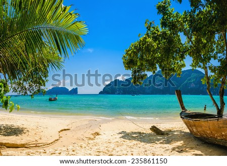 Exotic beach with palms and boats on azure water, Phi Phi Island, Phuket area, Thailand - stock photo
