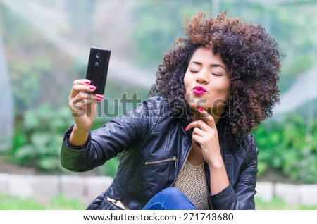 exotic beautiful young girl with dark curly hair taking selfie with her cell phone sitting in the garden - stock photo