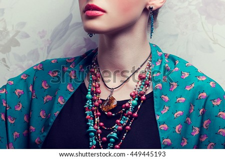 Exotic beauty concept. Beautiful young woman with bright make-up looking like well known Mexican artist posing over vintage background. Luxurious accessories. Close up. Studio shot