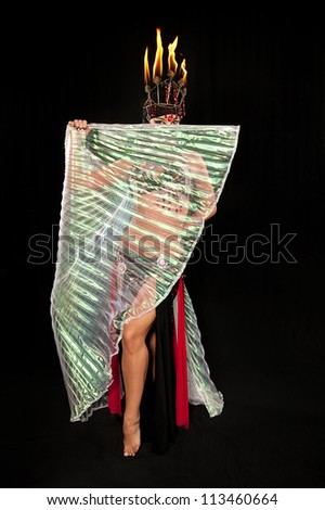 Exotic belly dancer wearing a red and black costume with hijab, fire headdress and Isis wings. Shot in the studio on an isolated black background. - stock photo