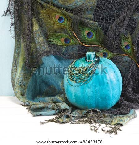 Exotic BOHO style Halloween display with a teal pumpkin, seed bead necklace, peacock feathers, netting and fringed fabric in blue and green jewel tones in square format