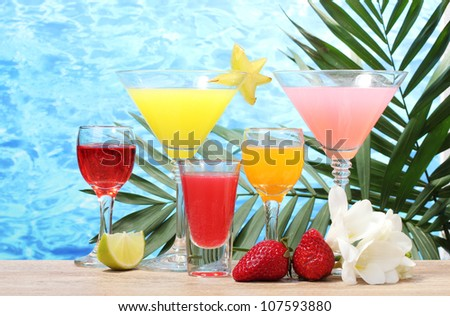 exotic cocktails and flowers on table on blue sea background