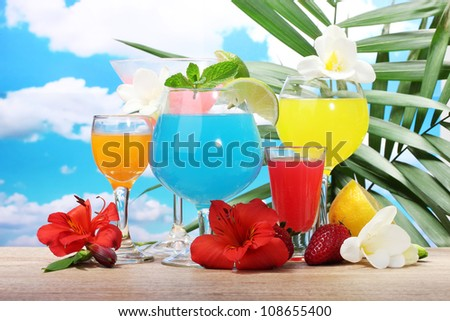 exotic cocktails and flowers on table on blue sky background - stock photo