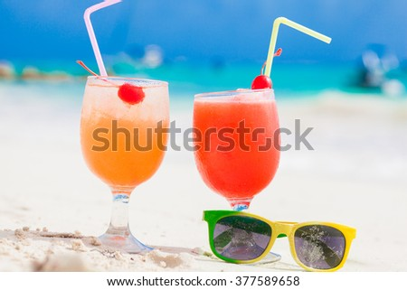 Exotic cocktails and sunglasses, caribbean beach on background - stock photo