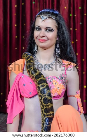 Exotic Female Dance Performer in Brightly Colored Costume with Large Constrictor Snake on Stage in front of Red Curtain - stock photo