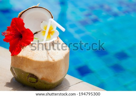 exotic fresh coconut shake and flower by the tropical pool - stock photo