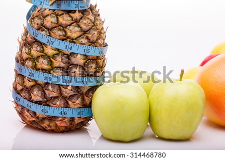 Exotic fresh fruits of one big pineapple green ripe apples and orange grapefruit with blue measuring tape as diet symbol on white studio background closeup copyspace, horizontal picture - stock photo