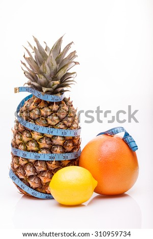 Exotic fresh fruits of one big pineapple yellow lemon and orange juicy grapefruit with blue measuring tape as diet symbol on white studio background closeup copyspace, vertical picture - stock photo