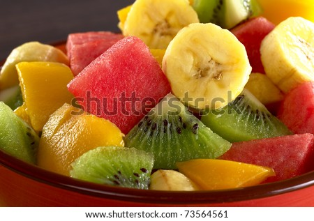 Exotic fruit salad of kiwi, banana, mango and watermelon pieces (Selective Focus, Focus on the banana, kiwi and watermelon slices in the middle)
