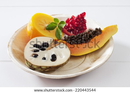 Exotic fruits, papaya, pomegranate, cherimoya, kaki slices on plate on white background - stock photo