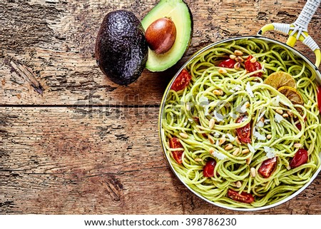 Exotic Italian spaghetti pasta with avocado pear, pine nuts, tomato and parmesan cheese served in a pan on a rustic wooden table with copy space, viewed from above - stock photo