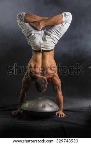 Exotic Male Drummer Doing Acrobatic Handstand on Steel Pan Drums, in Studio Isolated on Black Background