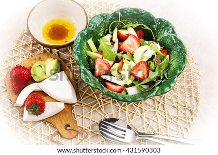 exotic salad with avocado, coconut, strawberry and rocket