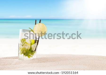 Exotic summer drink in sand, blur beach on background - stock photo