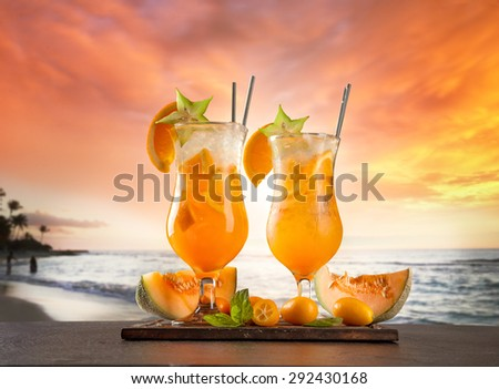 Exotic summer drinks served on stone. Blur beach as background - stock photo