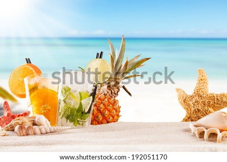 Exotic summer drinks with sea shells and stars, blur sandy beach on background - stock photo