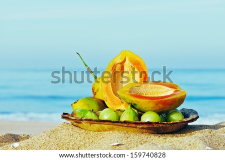 Exotic tropical fruit on the leaves plate on the sandy beach  - stock photo