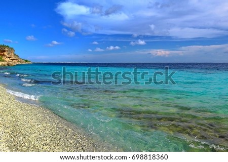Exotic tropical pebble beach with calm azure ocean. Blue sky and white clouds. Sunny day on the tropical vacation island.