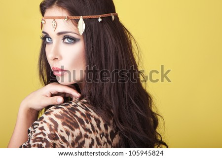 Exotic woman wearing a headband around her lovely wavy brunette hair and looking over her shoulder - stock photo
