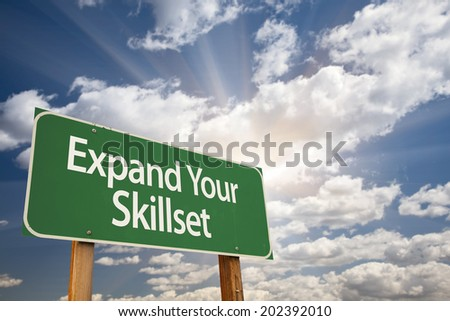 Expand Your Skillset Green Road Sign with Dramatic Clouds and Sky.