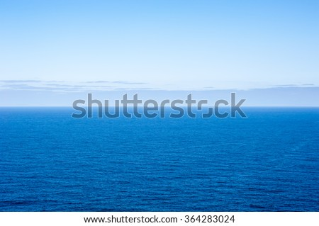 Expansive deep blue empty ocean seascape with layer of gray clouds forming along horizon in distance. - stock photo