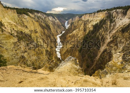 Expansive view of Lower Falls of the Yellowstone River, with pines and steep yellow cliffs, Wyoming. - stock photo