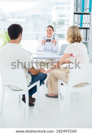 Expectant couple consulting female doctor in clinic - stock photo