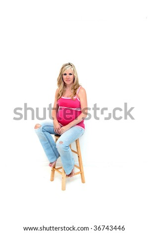 Expectant mom rests on a stool.  She is wearing grunge jeans and is barefoot.  Her jeans have holes at the knees and she is thinking wonderful thoughts about the coming baby.
