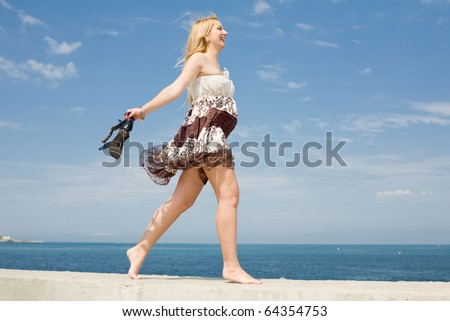 Expectant mother in brown dress walks along seashore - stock photo