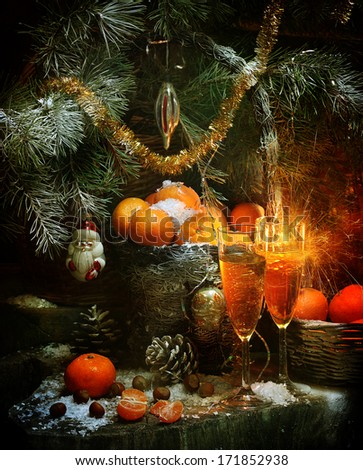 Expectation of new year - a wattled basket filled with fragrant ripe tangerines and invigorating champagne in beautiful transparent wine glasses under fluffy branches of a natural fur-tree - stock photo