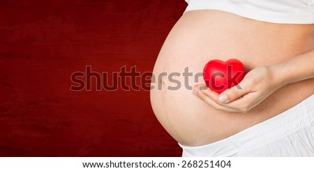 Expecting. Close up on pregnant belly. Woman expecting a baby holding a red heart with love. - stock photo