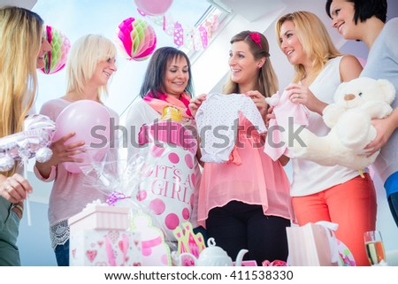 Expecting Mother with presents on baby shower party getting a romper suit, her friends sitting on couch - stock photo