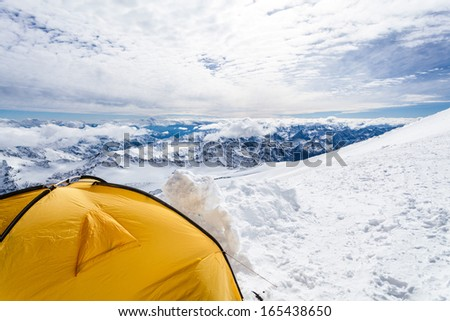 Expedition camping in tent on Mount Elbrus trail to the top, Mountain landscape in autumn or winter in Caucasus Mountains i Russia and Georgia, view from Elbrus(5642m) slopes on Pastuchov Rocks 4700m - stock photo