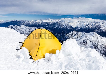 Expedition camping in tent on Mount Elbrus trail to the top, Mountain landscape in autumn or winter in Caucasus Mountains i Russia and Georgia, view from Elbrus(5642m) slopes on Pastuchov Rocks 4700m. - stock photo